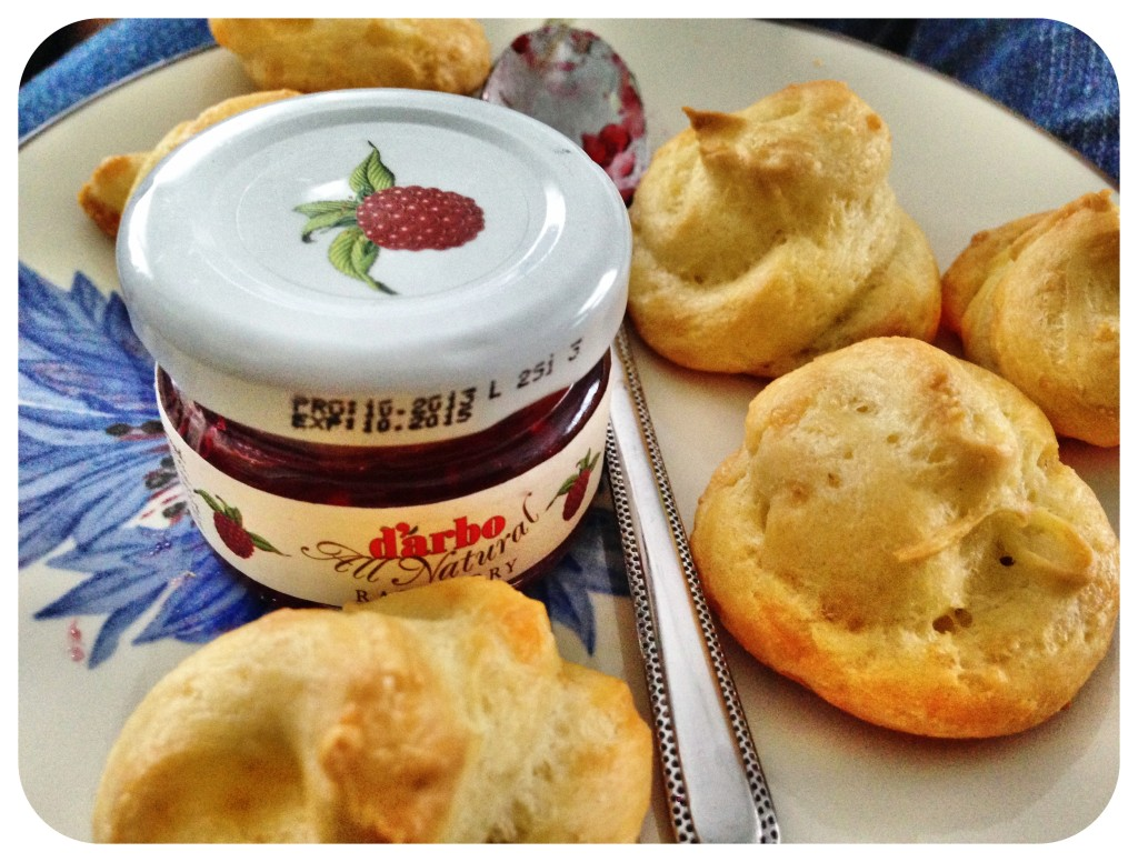 Cheese gougeres ready to eat, with a tiny side jar of jam.
