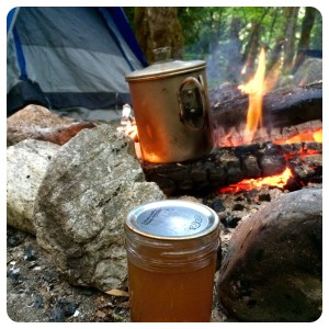 If you put the pre-mixed toddy ingredients in a glass jar you can heat it up near the fire to melt the honey before combining with water from the percolator.