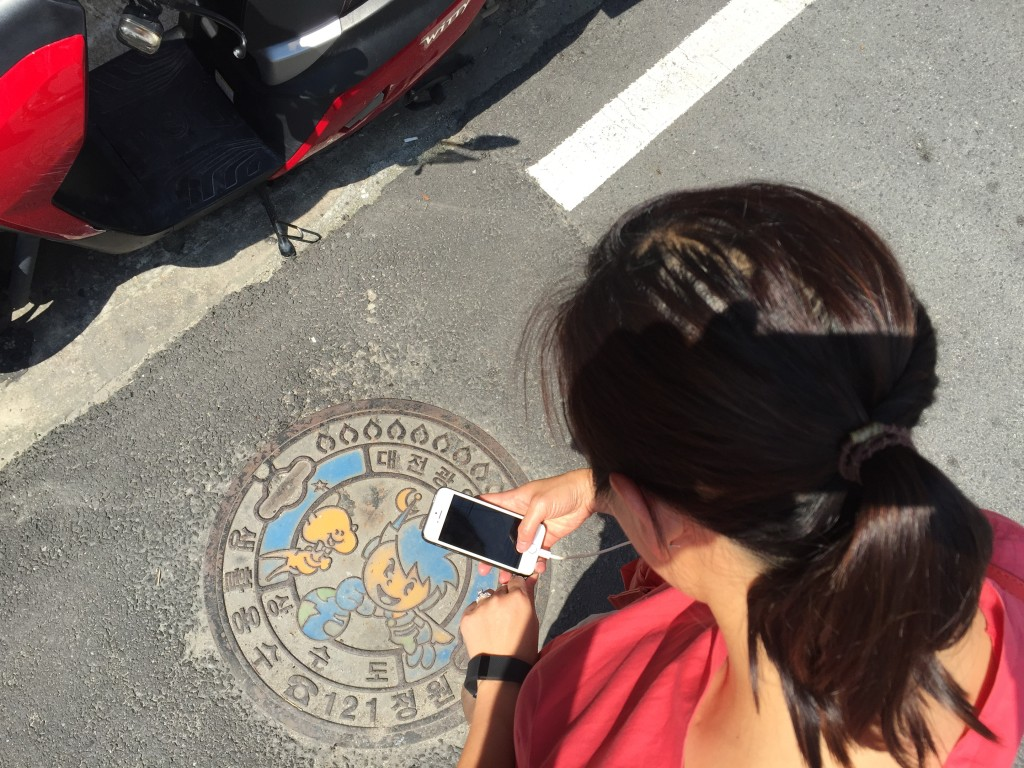 @Daejeon: K caught me mid-snap for another manhole cover shot. I <3 municipal street art. Look, they even colored it!