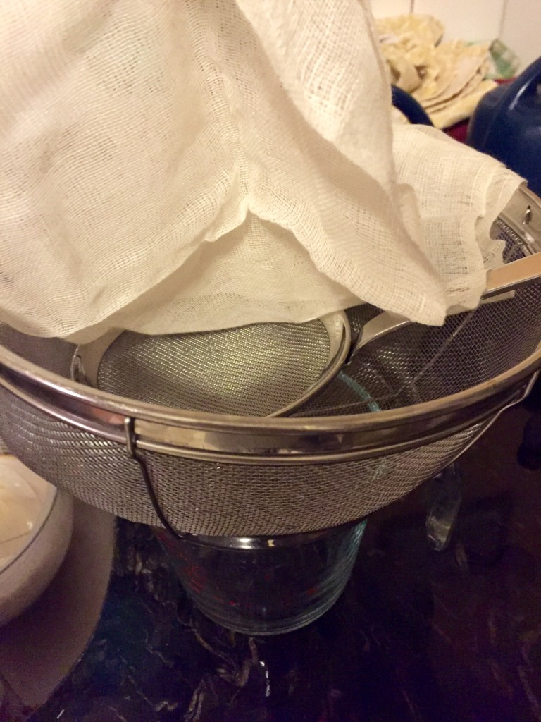 The straining setup: cup below, topped with colander, then soup sifter, then four layers of cheesecloth.