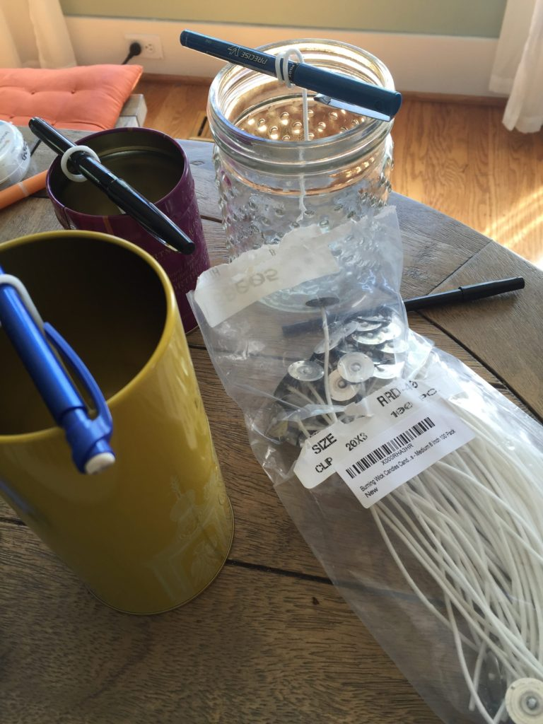 Pre-prep your candle tins thus: with wicks wrapped around pencils or pens.